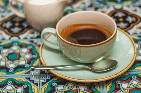 Photo for Ceramic cup with hot coffee on saucer with spoon, close-up - Royalty Free Image