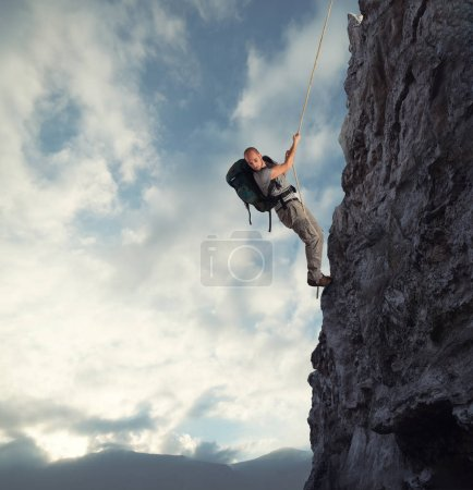 Man climbs a high danger mountain with a rope