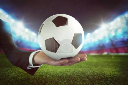 Sport bets. Soccer ball on the hand of a businessman with stadium background