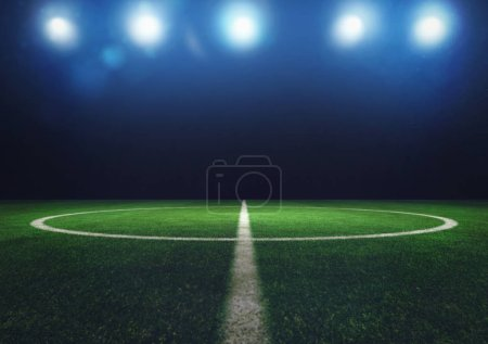 Midfield of grass soccer field at night with headlights