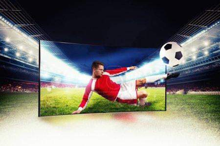 Photo pour Un footballeur sort de la télé pour donner un coup de pied au ballon - image libre de droit