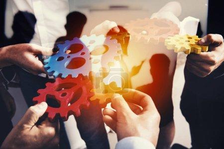 Photo pour Le travail d'équipe des gens d'affaires travaillent ensemble et combinent des pièces d'engrenages. Concept de partenariat et d'intégration. double exposition - image libre de droit