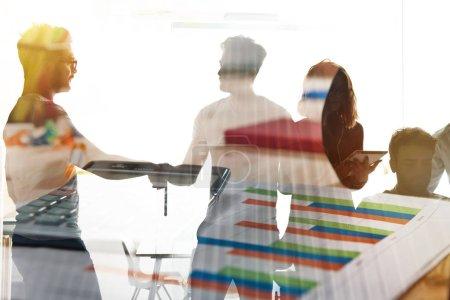 Photo pour Handshaking homme d'affaires dans le bureau avec des feuilles de travail fond - image libre de droit