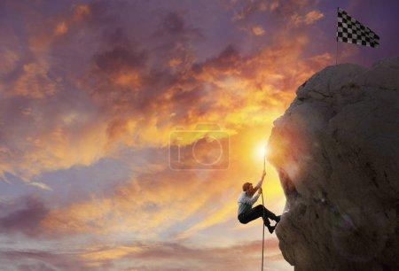 Photo pour Un homme d'affaires grimpe une montagne pour obtenir le drapeau. Atteinte de l'objectif commercial et concept de carrière difficile - image libre de droit