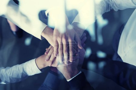 Photo for Business people putting their hands together in office. Concept of startup, integration, teamwork and partnership. Double exposure - Royalty Free Image