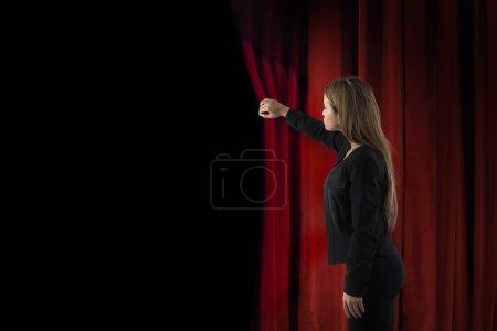 Photo pour Femme rideaux rouges ouverts de la scène de théâtre pour commencer le spectacle - image libre de droit