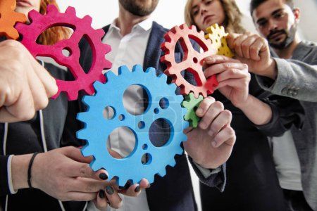 Photo for Teamwork of businesspeople work together and combine pieces of gears. Partnership and integration concept - Royalty Free Image