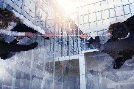 Photo pour Des hommes et des femmes d'affaires rivaux se disputent le commandement en tirant la corde. double exposition - image libre de droit