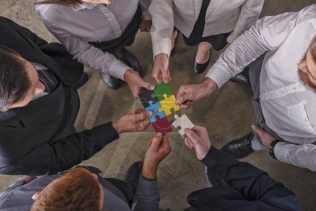 Foto de Empresarios trabajando juntos para construir un rompecabezas de colores. Concepto de trabajo en equipo, asociación, integración y puesta en marcha . - Imagen libre de derechos