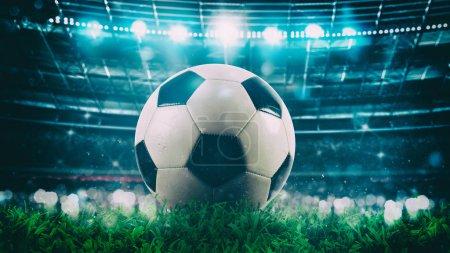 Nahaufnahme eines Fußballs in der Mitte des Stadions, beleuchtet von den Scheinwerfern