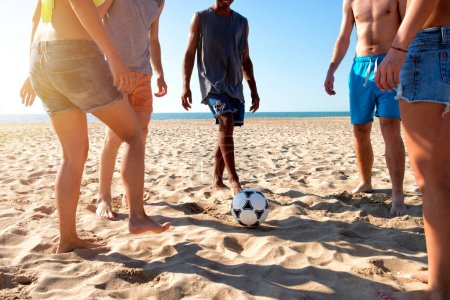 Photo for Group of happy friends playing soccer at the beach - Royalty Free Image