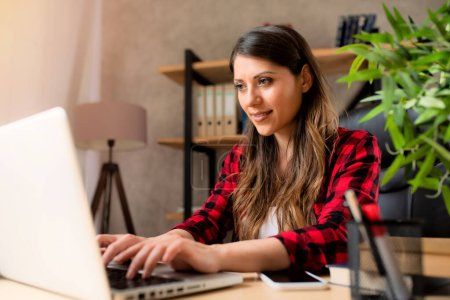 Photo for Girl works at home with a laptop - Royalty Free Image