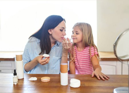 Cute smiling mother and daughter applying face cream together