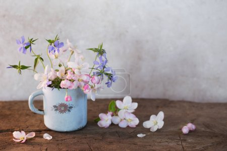 spring flowers in cup on wooden table