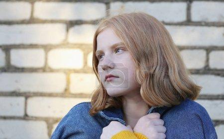 sad teenager girl on background brick wall