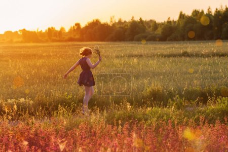Photo for Teenager girl in summer field at sunset - Royalty Free Image