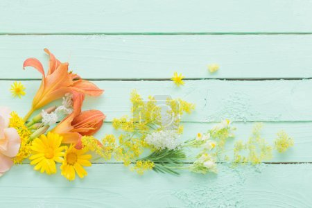 Photo for Yellow and orange flowers on green wooden background - Royalty Free Image