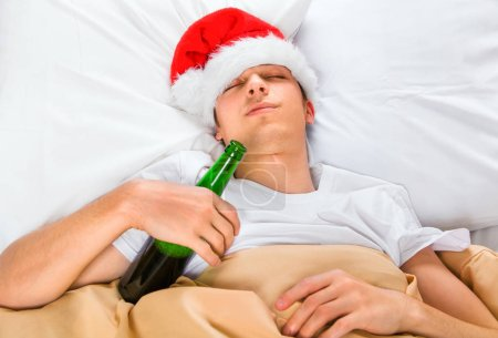 Young Man in Santa Hat sleep in the Bed with a Beer Bottle