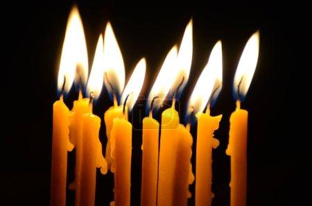 Photo pour Brûler des bougies dans une église sur un fond sombre - image libre de droit