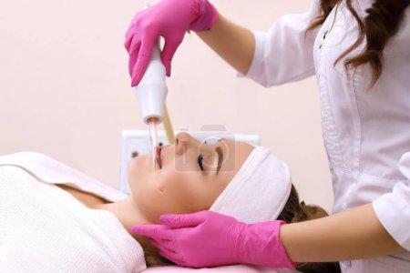 Photo pour Personnes, beauté, spa, cosmétologie et concept de technologie - gros plan de belle jeune femme couchée les yeux fermés ayant massage du visage par masseur dans le spa . - image libre de droit