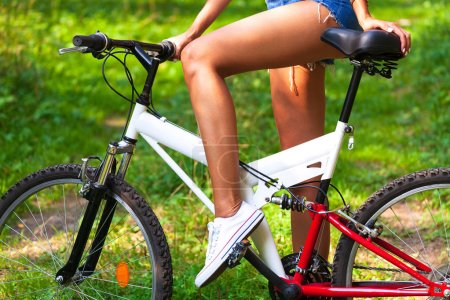Photo for Woman with long legs and bicycle in a summer park - Royalty Free Image