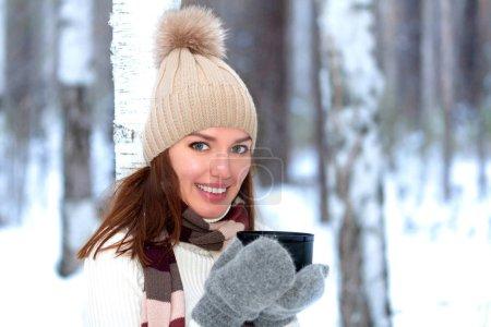 Photo pour Souriant jolie jeune femme avec une tasse de thé chaud ou de café pose dans une forêt ou un parc d'hiver - image libre de droit