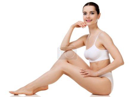 Photo pour Concept bien-être et beauté, belle femme mince en sous-vêtements blancs assise sur un sol blanc. - image libre de droit