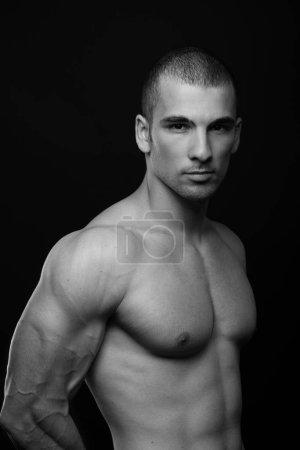 Photo pour Athlétique torse nu mâle modèle flexion muscles - image libre de droit