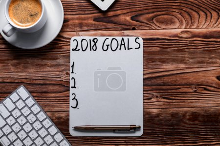 2018 GOALS on his notebook. New year resolutions concept. Top view.