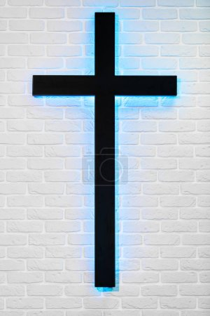 holy cross hanging on brick white wall