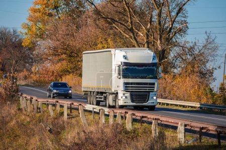 Photo pour Arrivée camion blanc sur la route dans un paysage rural au coucher du soleil - image libre de droit