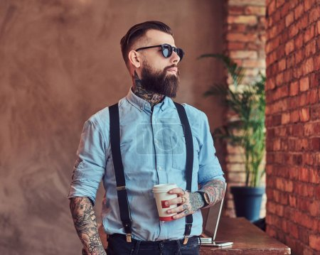 Old-fashioned tattooed hipster wearing a shirt and suspenders, in a sunglasses, standing with a cup of a coffee near a desk with a laptop, looking out the window in an office with loft interior.