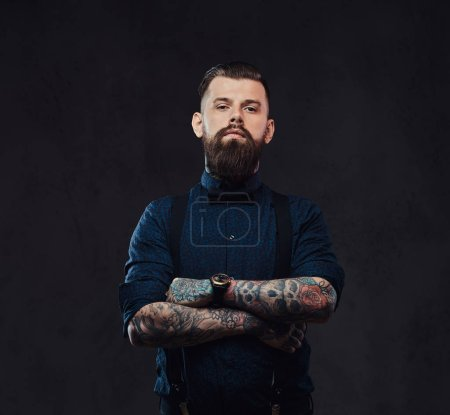 Portrait of a handsome old-fashioned hipster in a blue shirt and suspenders, standing with crossed arms in a studio. Isolated on a dark background.