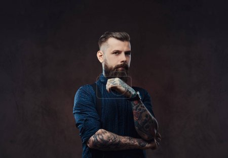 Pensive handsome old-fashioned hipster in a blue shirt and suspenders, standing with hand on chin in a studio. Isolated on a dark background.