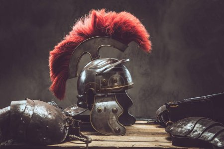Photo for Complete combat equipment of the ancient Greek warrior lie on a box of wooden boards. Isolated on a dark background. - Royalty Free Image