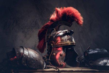 Photo pour Équipement complet de combat du guerrier grec antique reposent sur une boîte de planches en bois. Isolé sur un fond sombre. - image libre de droit