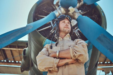 Handsome pilot in a full flight gear standing with crossed arms near military airplane.