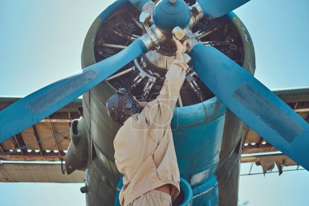 Pilot or mechanic in a full flight gear checks the propeller of his retro military aircraft before the flight.