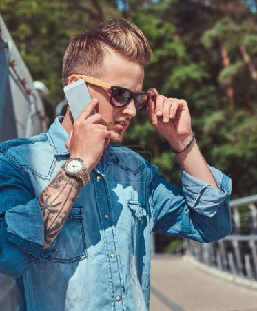 Photo for Young handsome fashionable hipster with stylish haircut in sunglasses talking by phone while standing on a footway. - Royalty Free Image