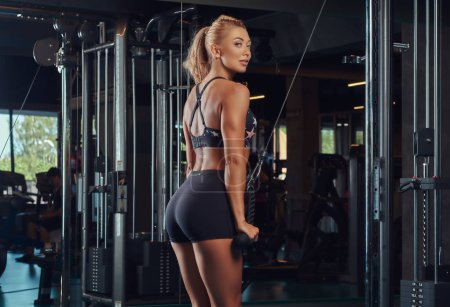 Athletic blonde woman in sportswear doing exercise on the triceps on the crossover machine in the gym.