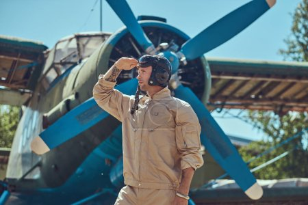 Valiant handsome pilot in a full flight gear standing near retro military airplane and looks away.