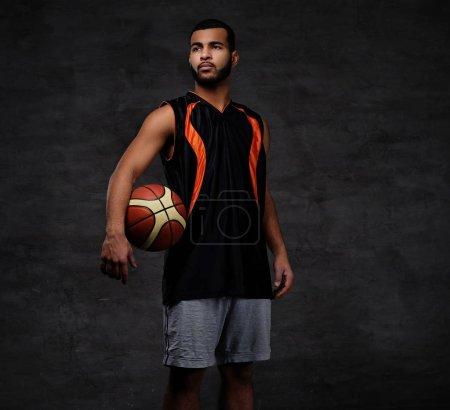 Photo pour Portrait d'un sportif afro-américain. Basketball joueur en vêtements de sport avec une balle sur un fond sombre . - image libre de droit