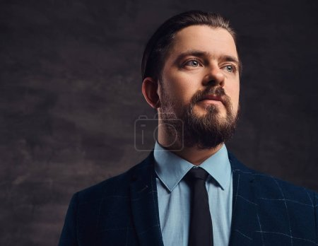 Photo for Close-up portrait of a handsome middle-aged man with beard and hairstyle dressed in an elegant formal suit on a textured dark background in studio. - Royalty Free Image
