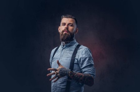 Portrait of a handsome old-fashioned hipster in a blue shirt and suspenders. Isolated on a dark background.