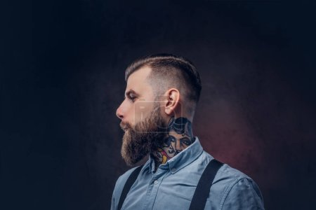 Profile of a handsome old-fashioned hipster in a blue shirt and suspenders. Isolated on a dark background.