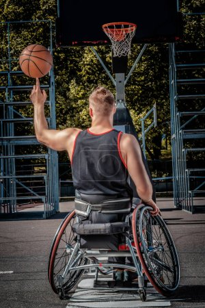 Back view of a disabled basketball player in a wheelchair spinning basketball on his finger on open gaming ground.