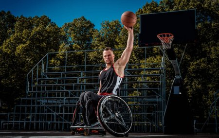 Cripple basketball player in a wheelchair holds a ball on open gaming ground.