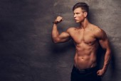 Strong shirtless young man model with nice muscular body showing his bicep at a studio. Isolated on a dark background.
