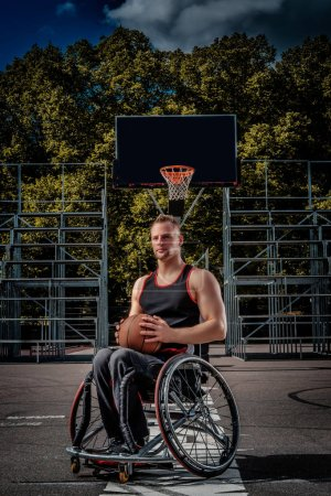 Portrait of a disabled basketball player in a wheelchair on an open gaming ground.