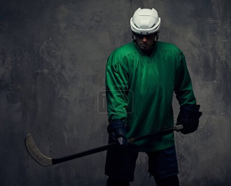 Professional hockey player trains in full equipment with gaming stick. Isolated on a gray background.